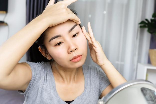 Aziatische vrouw van 40 jaar die gezichtsmassage doet en haar gezicht optilt