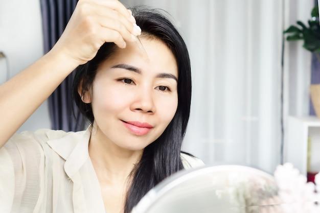 Aziatische vrouw van 40 jaar die serumcollageen op haar huid aanbrengt op anti-rimpels