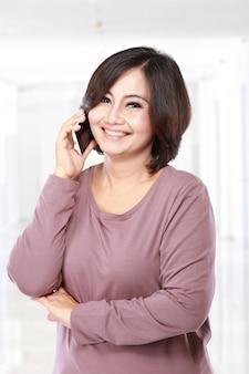 Aziatische vrouw van middelbare leeftijd aan de telefoon