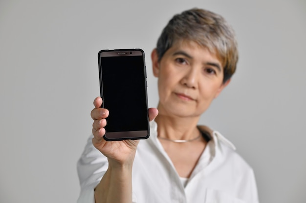 Aziatische vrouw van middelbare leeftijd die een leeg smartphonescherm toont terwijl ze naar de camera kijkt die op een witte achtergrond wordt geïsoleerd. focus op een smartphone