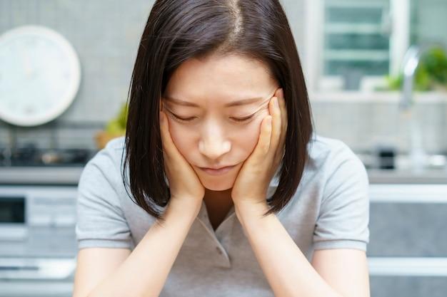 Aziatische vrouw van middelbare leeftijd met een vermoeide blik in de kamer