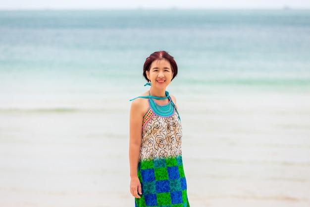 Aziatische vrouw van middelbare leeftijd ontspannen op chaweng beach in koh samui, thailand.