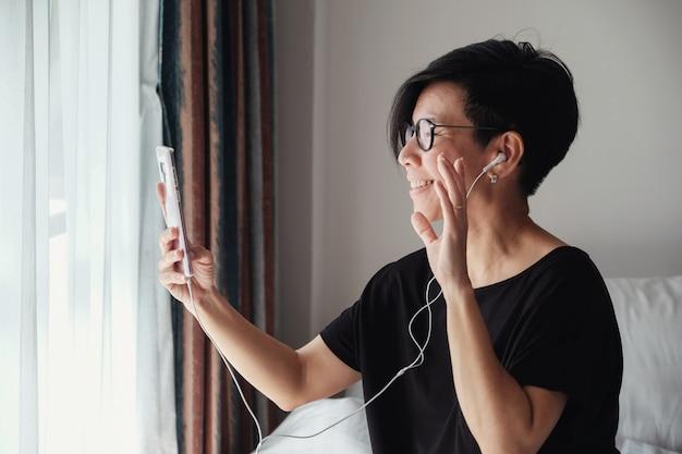 Aziatische vrouw van middelbare leeftijd video maken thuis bellen