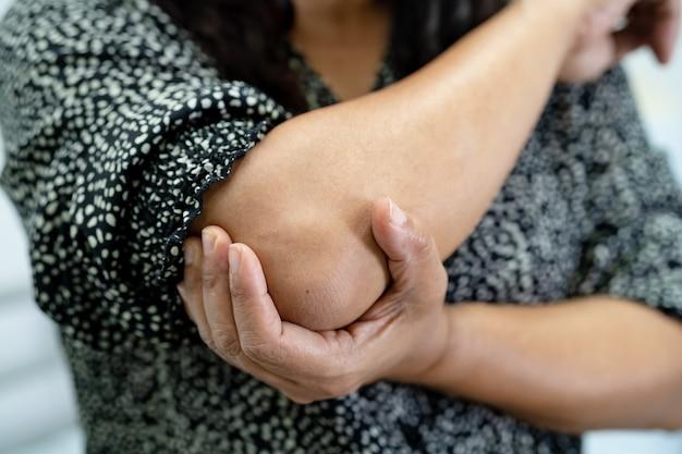 Aziatische vrouw van middelbare leeftijd vrouw patiënt aanraken en voelen pijn haar elleboog en arm, gezond medisch concept.