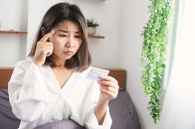 Aziatische vrouw vergeet anticonceptiepil te nemen met een bezorgd gezicht