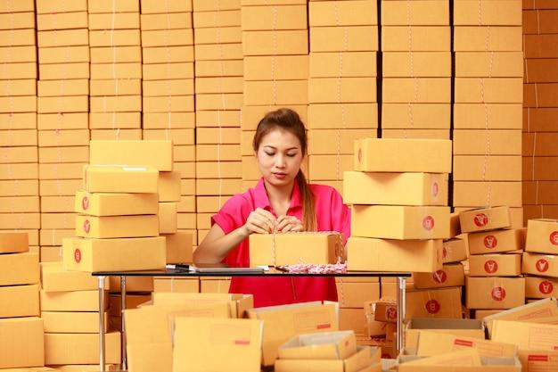 Aziatische vrouw verpakkingsdozen thuis in e-commerce online winkelbedrijf