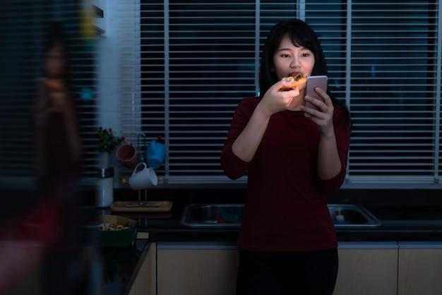 Aziatische vrouw virtuele happy hour ontmoeting en eten bezorgpizza uit de doos online met vriend of het nemen van foto met behulp van mobiele telefoon in de keuken 's nachts tijdens de isolatie van het huis. Premium Foto
