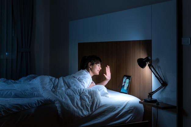 Aziatische vrouw virtuele happy hour vergadering online samen met haar vriend in videoconferentie tot welterusten voor het slapen 's nachts