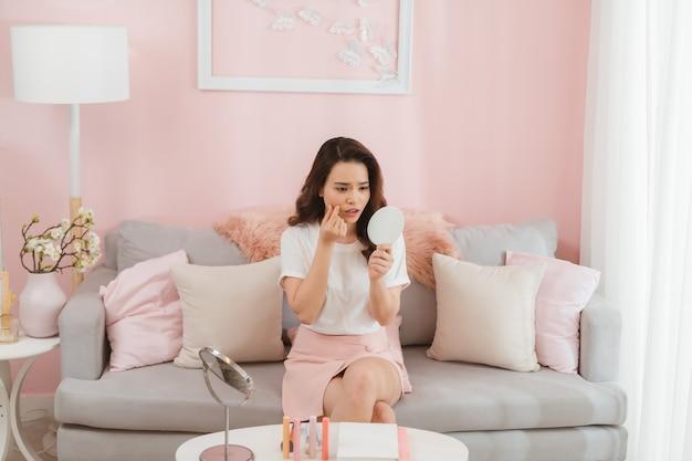 Aziatische vrouw voelt zich verdrietig omdat haar huid acne heeft