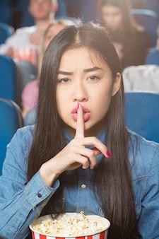 Aziatische vrouw vraagt om stilte met zwijgend gebaar bij de plaatselijke bioscoop
