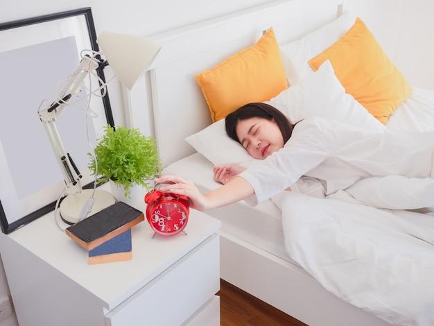Aziatische vrouw wakker in de ochtend en zet de wekker