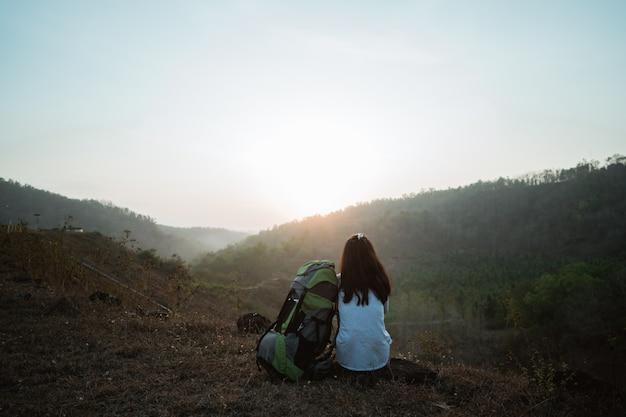 Aziatische vrouw wandelaar alleen zitten genieten van de schoonheid van de natuur