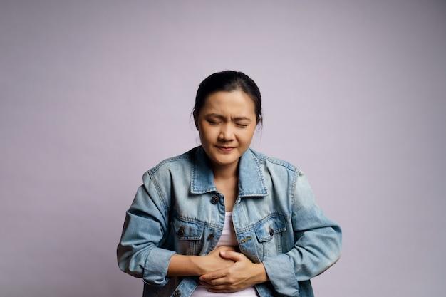 Aziatische vrouw was ziek met buikpijn staande geïsoleerd.