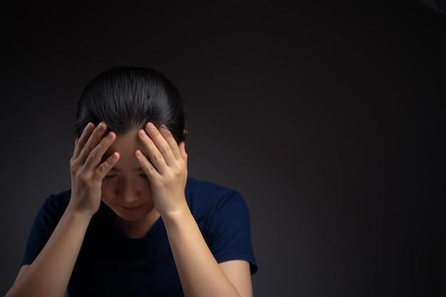Aziatische vrouw was ziek met hoofdpijn aanraken van haar hoofd staande geïsoleerd op de achtergrond.