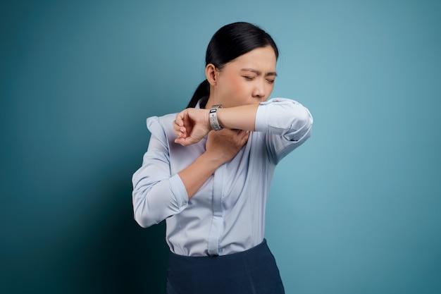 Aziatische vrouw was ziek met koorts geïsoleerd op blauw.