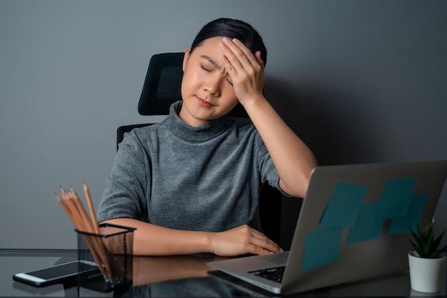 Aziatische vrouw was ziek van hoofdpijn, raakte haar hoofd aan, werkte op een laptop op kantoor