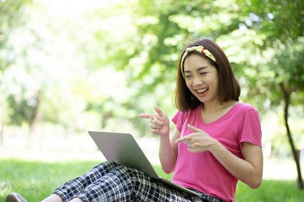 Aziatische vrouw wees handen naar laptop scherm voor hallo haar vrienden in videogesprek en lachend gezicht
