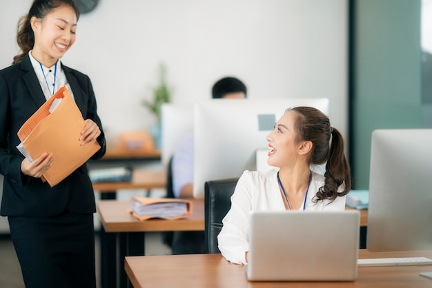 Aziatische vrouw werkt samen op kantoor met docoment en computer notitieboek, deze afbeelding kan gebruiken voor zaken, werken, vrouw en teamwerk in een bedrijfsconcept