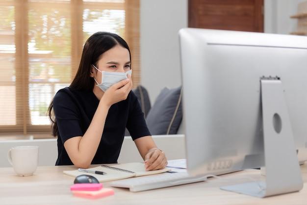 Aziatische vrouw werkt vanuit huis. bij ziekten met aandoeningen van de luchtwegen een medisch masker opzetten, hoesten voor een computer.