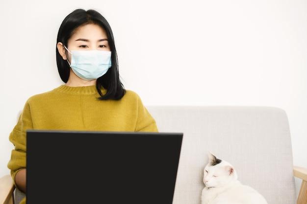Aziatische vrouw werkt vanuit huis met beschermend masker