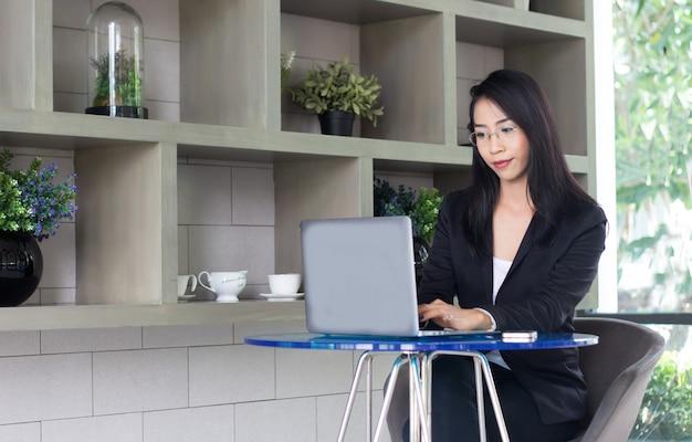Aziatische vrouw werkt vanuit huis met draadloze technologie met laptop en internet in een pandemie van het coronavirus in de woonkamer