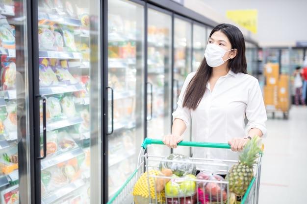 Aziatische vrouw winkelen met masker veilig kopen voor boodschappen, veiligheidsmaatregelen in de supermarkt.