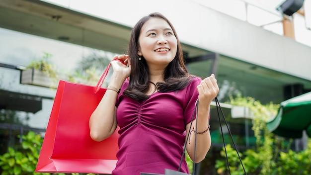 Aziatische vrouw winkelen mode in winkelcentrum met haar vriend bellen
