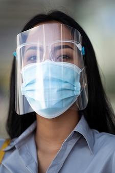 Aziatische vrouw wordt beschermd door covid 19 en hij draagt een gezichtsmasker.