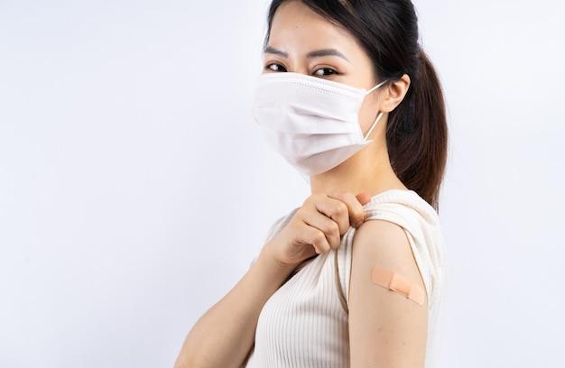 Aziatische vrouw wordt ingeënt tegen covid 19 op wit