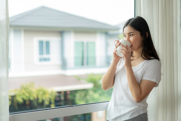 Aziatische vrouw wordt volledig uitgerust wakker in haar bed en opent de gordijnen op de vensterbank en kijkt uit het raam