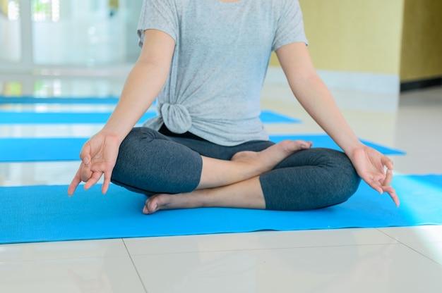 Aziatische vrouw yoga ademhaling en meditatie alleen in fitness gym. indoor oefening en training voor gezond en welzijn.