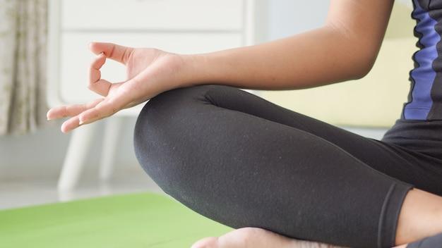 Aziatische vrouw yoga handen oefenen thuis