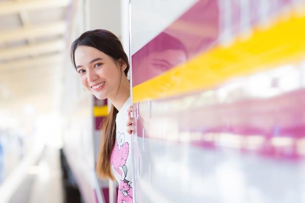 Aziatische vrouw zegt hallo tegen haar familie omdat ze met de trein in de stad werkt of ze komt aan en zegt welkom