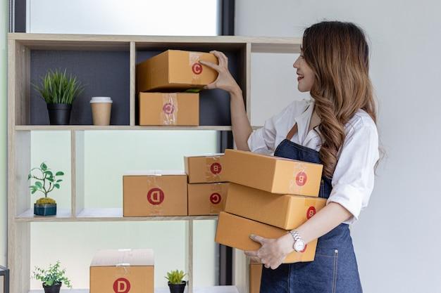 Aziatische vrouw zet een verpakt pakket op een plank om het klaar te maken voor bezorging, bezit een online winkel, ze verpakt en verzendt het via een particulier transportbedrijf. online verkoop en online winkelconcepten.