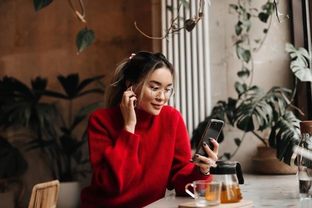 Aziatische vrouw zet op draadloze oortelefoon en houdt smartphone