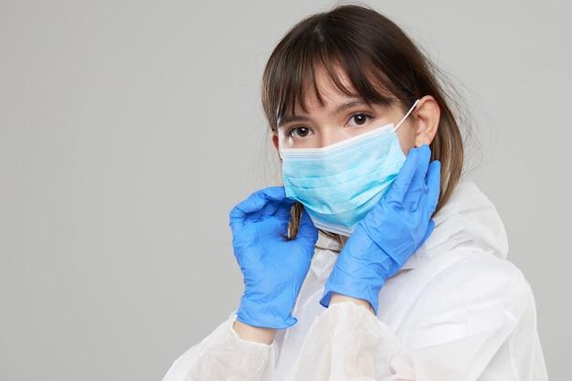 Aziatische vrouw zet op een beschermend masker en pak. beschermd tegen griep, ebola, tuberculose, virus. persoonlijke beschermingsmiddelen tegen biologisch gevaar.