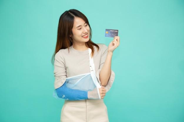 Aziatische vrouw zette een zachte spalk op vanwege een gebroken arm en hield een creditcard vast.