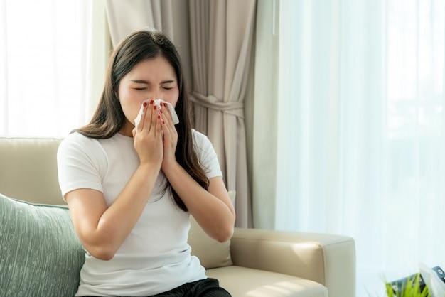 Aziatische vrouw ziek en verdrietig met niezen