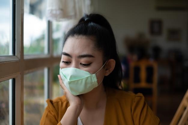 Aziatische vrouw zit en zet een medisch masker op