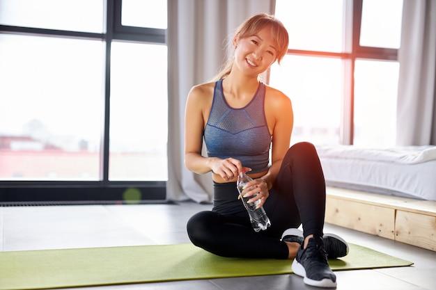 Aziatische vrouw zit op yoga mat met fles water, glimlachend, sportieve top en leggins dragen, ontspannen tijd
