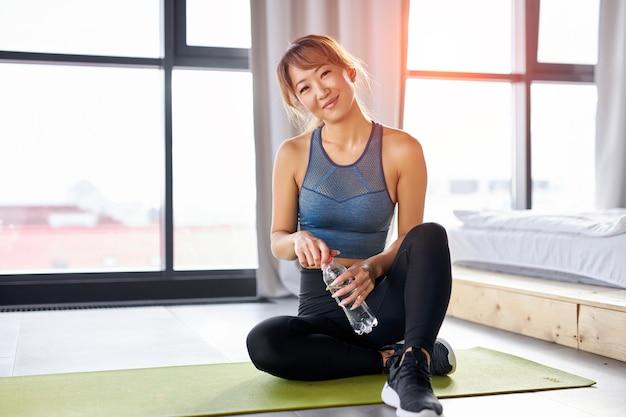 Aziatische vrouw zit op yogamat met waterfles, kijkt glimlachend, sportieve top en leggings dragen, ontspan tijd