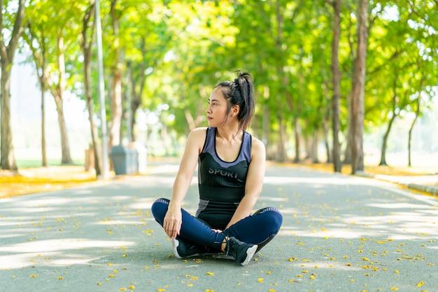 Aziatische vrouw zitten en ontspannen in sportkleding na het sporten in het park