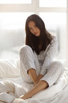 Aziatische vrouw zitten in het bed binnenshuis