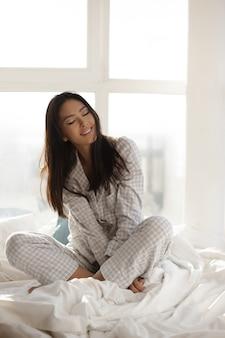 Aziatische vrouw zittend op bed thuis