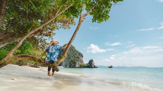 Aziatische vrouw zittend op de boom en genieten met prachtige zee natuur in haar vakantie.