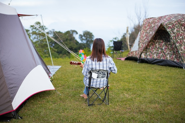 Aziatische vrouw zittend op een picknickstoel en gitaar spelen tijdens het kamperen met familie op de camping in de prachtige natuur.