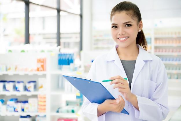 Aziatische vrouwelijke apotheker die in apotheek of apotheek werkt