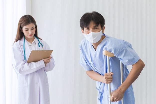 Aziatische vrouwelijke arts controleert het lopen van een mannelijke patiënt die een gezichtsmasker draagt terwijl hij een rollator gebruikt