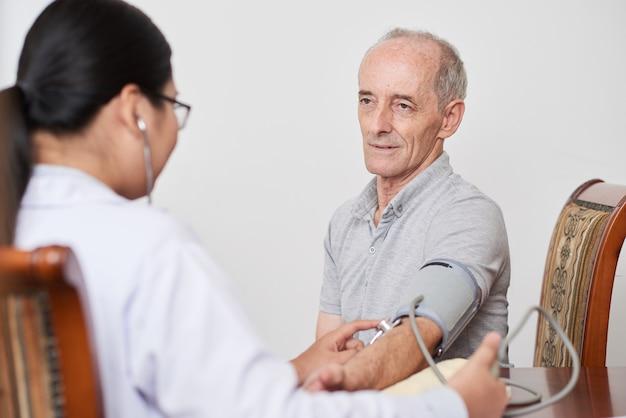 Aziatische vrouwelijke arts die de bloeddruk van de hogere kaukasische mannelijke patiënt neemt