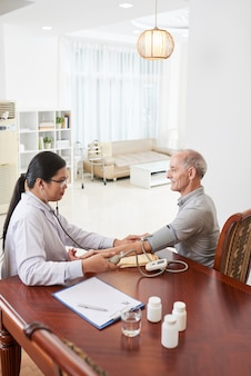 Aziatische vrouwelijke arts die de bloeddruk van de patiënt meet tijdens huisbezoek
